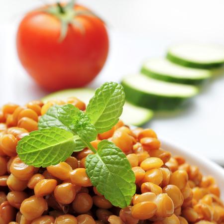 leguminosas: Primer plano de un tazón con lentejas cocidas y algunos vegetales crudos en el fondo