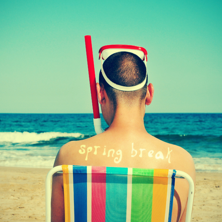 free diving: a man wearing a diving mask and a snorkel seated in a deckchair on the beach with the text spring break written in his back as a tan mark, with a retro effect