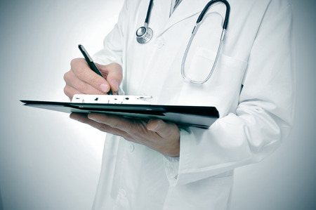 a doctor writing in a clipboard photo