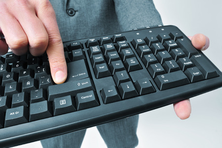 man wearing a suit pressing the enter key of a computer keyboard Stock Photo