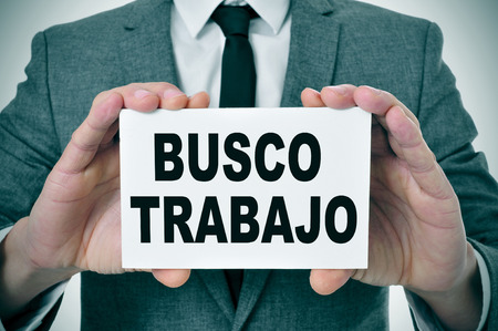 trabajo: a man wearing a suit holding a signboard with the text busco trabajo, looking for a job written in spanish Stock Photo