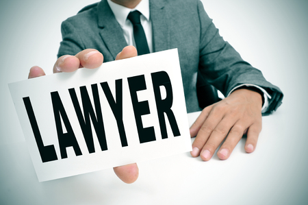 a man wearing a suit sitting in a desk holding a signboard with the word lawyer written in it photo