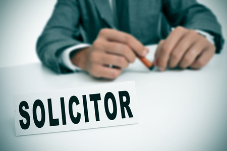 solicitor: a man wearing a suit sitting in a desk with a desktop nameplate in front of him with the word solicitor Stock Photo