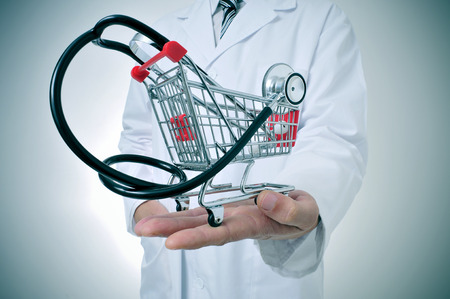 preventive medicine: doctor holding in his hand a shopping cart with a stethoscope inside, depicting the health care industry concept
