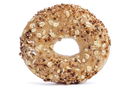 bagel: a brown bagel topped with different seeds, such as sesame and poppy seeds, on a white background Stock Photo