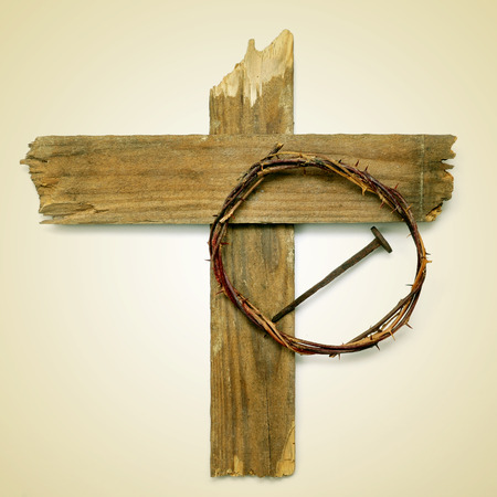 the Holy Cross, the crown of thorns and a nail depicting the passion of Jesus Christ on a beige background, with a retro effect photo