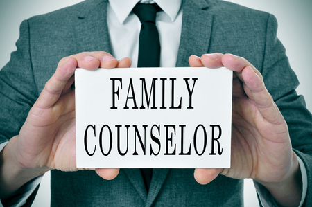 family constellation: a man wearing a suit sitting in a desk with a desktop nameplate in front of him with the word family counselor
