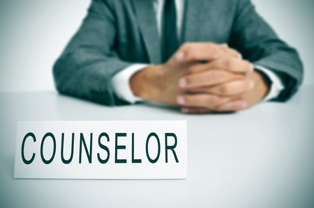 a man wearing a suit sitting in a desk with a desktop nameplate in front of him with the word counselor photo