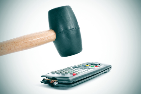 cable tv: someone broking a remote control with a hammer Stock Photo