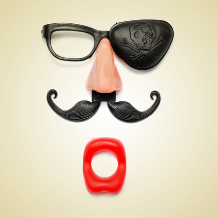 a funny face formed with fake mouth, nose and glasses with mustache and pirate patch on a beige , with a retro effect photo