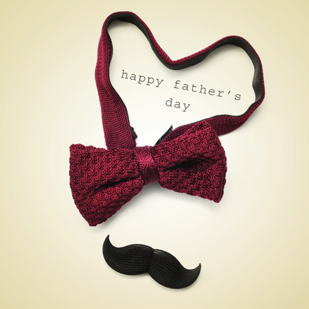 a bow tie forming a heart, a mustache and the sentence happy fathers day in a beige background, with a retro effect Stock Photo