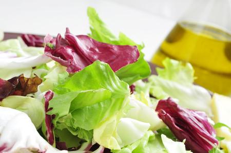 endivia: portarretrato de una placa con mezclum, una mezcla de hojas de ensalada variada, en una mesa de juego con una botella de aceite de oliva Foto de archivo