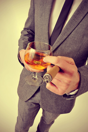 a man wearing a suit with a cigar and a glass with brandy whit a retro effect photo