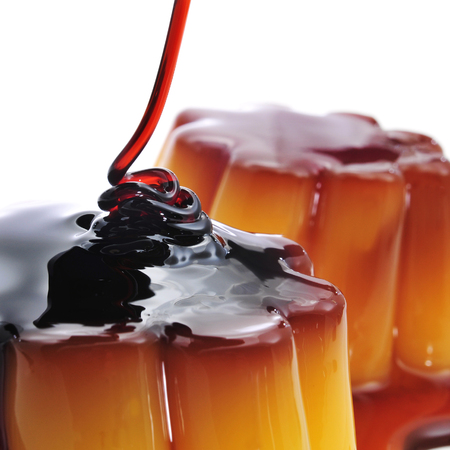 flavoured: closeup of a creme caramel topped with caramel sauce isolated on white
