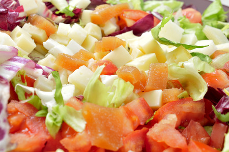 cornsalad: closeup of a salad with diced tomato, cheese and quince jelly