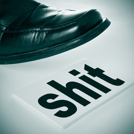 shit: a man foot wearing a black shoe stepping on a signboard with the word shit written in it