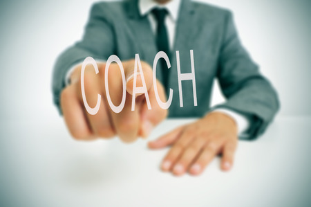 businessman sitting in a desk pointing the word coach written in the foreground photo