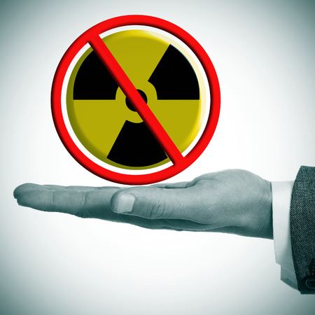 a man hand with a no nuclear power sign in his hand photo
