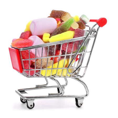 candy shop: shopping cart full of candies on a white background