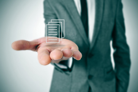 a businessman holding a document icon in his hand photo
