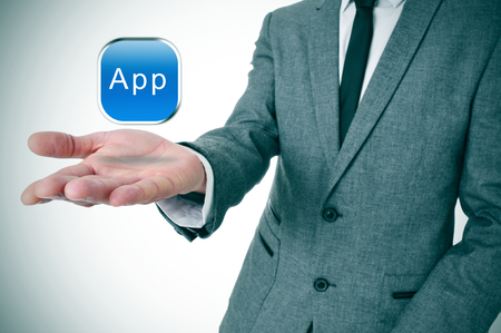 a businessman with an icon with the word app in his hand photo
