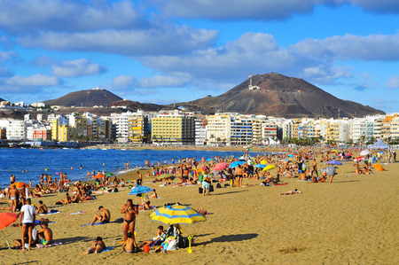 bathers: LAS PALMAS, SPAIN - OCTOBER 13: Bathers in Las Canteras Beach on October 13, 2013 in Las Palmas de Gran Canaria, Spain. Due to the tropical weather, the locals can go to the beach almost all year