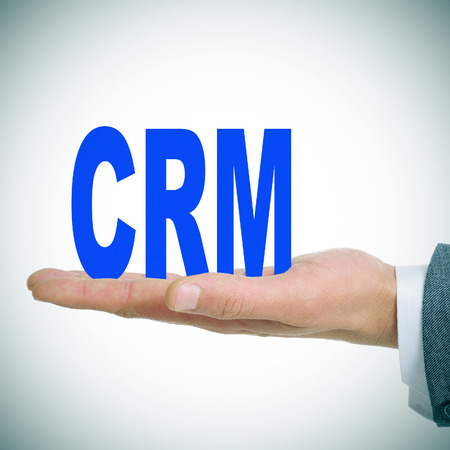 a man holding the acronym CRM for Customer Relationship Management photo