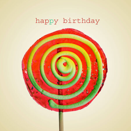 a colorful lollipop with a spiral pattern with the text happy birthday on a beige background, with a retro effect photo