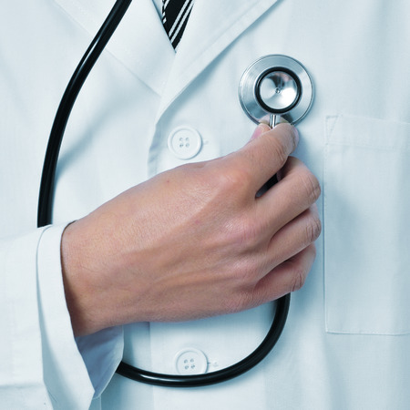 self exam: a doctor auscultating himself with a stethoscope Stock Photo