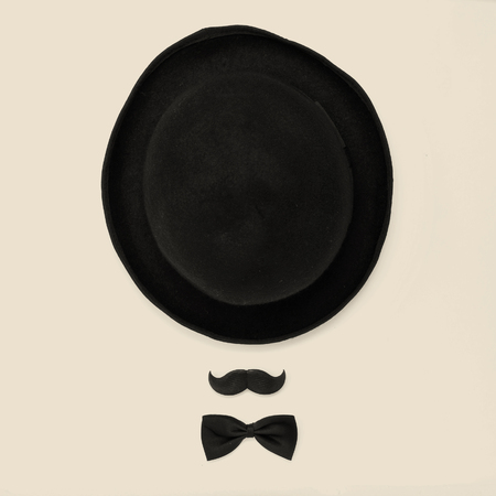 a bowler hat, a mustache and a bowtie on a beige background depicting a gentleman or a hipster guy, with a retro effect photo