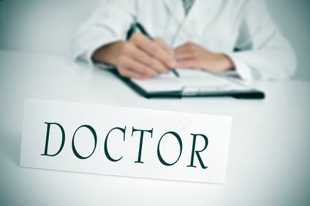 prescribe: a doctor sitting in the desk of his consulting room writing in a clipboard and a nameplate with the word doctor written in it