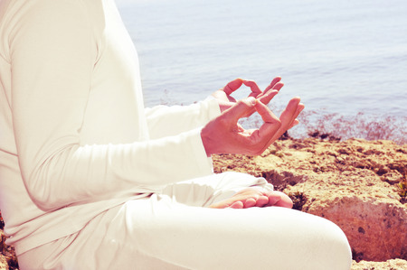 someone meditating in front of the sea, with a retro effect Stock Photo - 26711409