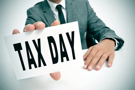 taxable: a businessman sitting in a desk showing a signboard with the text tax day written in it