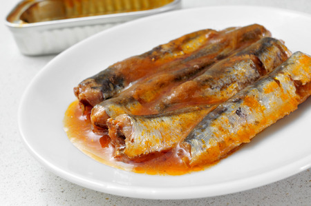 sprat: closeup of a pile of canned sardines in a plate