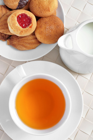 british food: a cup with tea and some biscuits in a plate, on a set table