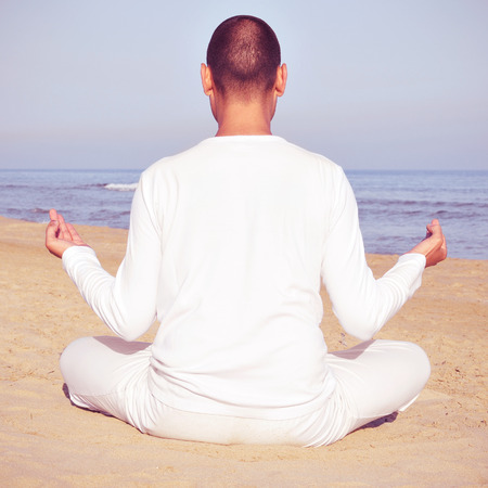 yogi aura: someone meditating in front of the sea, with a retro effect Stock Photo