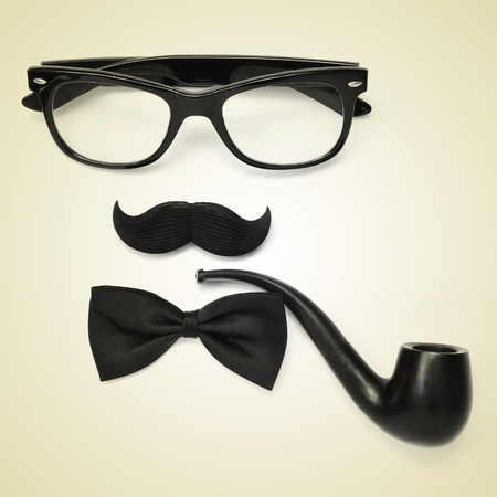 a pair of glasses, a mustache, a bowtie and a smoking pipe on a beige background depicting a gentleman or a hipster guy, with a retro effect photo