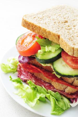 carnes y verduras: un sándwich con verduras y chorizo ??español y salchichón, sobre un fondo blanco