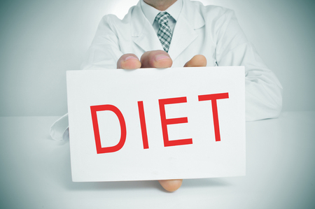 nutritionist: a man wearing a white coat sitting in a desk showing a signboard with the word diet written in it