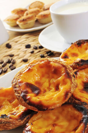 closeup of some pasteis de nata and some pasteis de feijao, typical Portuguese pastries, on a set table photo