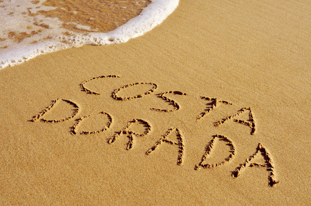 costa: Costa Dorada, the name of an area of the Mediterranean coast of Spain, written in the sand of a beach