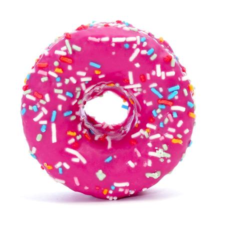 een donut bedekt met een roze glazuur en hagelslag van verschillende kleuren op een witte achtergrond