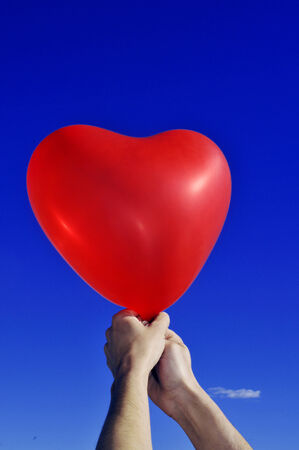 someone holding a red heart-shaped balloon over the blue sky photo
