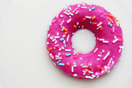 doughnut: a donut coated with a pink frosting and sprinkles of different colors soaking in milk Stock Photo