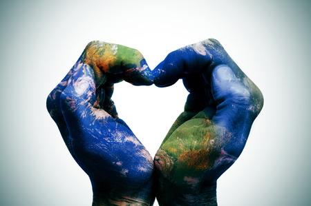 une carte du monde dans les mains de l'homme formant un coeur (carte de la terre fournie par la NASA) Banque d'images