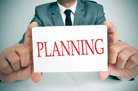pensamiento estrategico: hombre de negocios sentado en un escritorio que muestra un letrero con la planificación texto escrito en ella