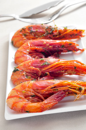gambas: closeup of a plate with spanish shrimps cooked with garlic and parsley on a set table Stock Photo