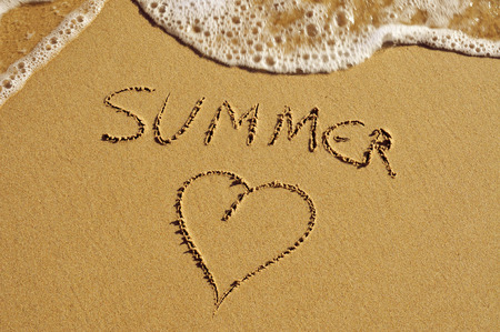 the word summer and a heart carved in the sand of a beach photo