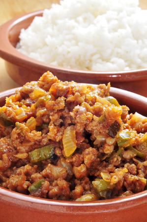 closeup of an earthenware plate with picadillo, a traditional dish in many latin american countries, and a bowl with rice in the background