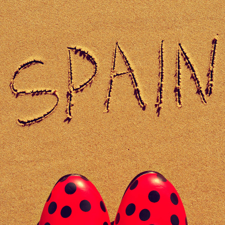 flamenco shoes and the word spain written in the sand of a beach photo